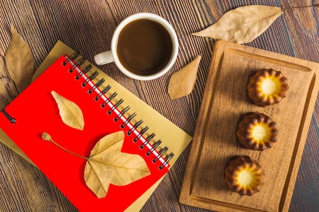 Gebäck in der nähe von notizblöcken und kaffee ...