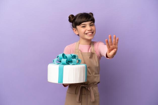 Gebäck kleines mädchen, das einen großen kuchen lokalisiert auf lila wand glücklich hält und vier mit den fingern zählt
