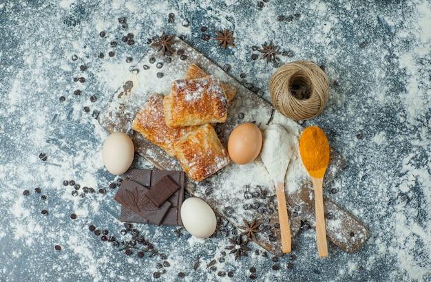Gebäck mit mehl, schokolade, gewürzen, eiern, faden auf beton und schneidebrett, draufsicht.