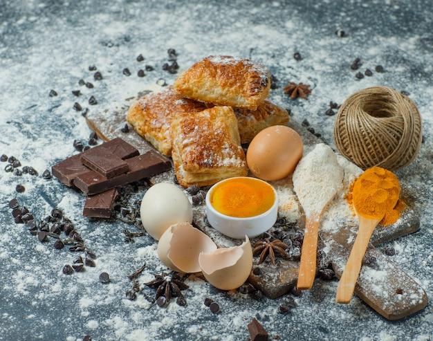Gebäck mit mehl, schokolade, gewürzen, eiern, faden-hochwinkelansicht auf beton und schneidebrett