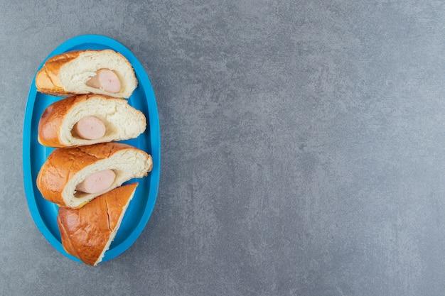 Gebäck mit würstchen in vier stücke geschnitten.