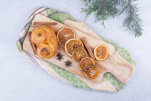 Gebäck mit zimtstangen, nelken und orangen auf holzbrett.