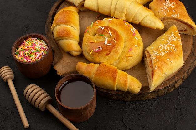 Gebäck und croissants von oben auf dem braunen schreibtisch und dem dunklen boden