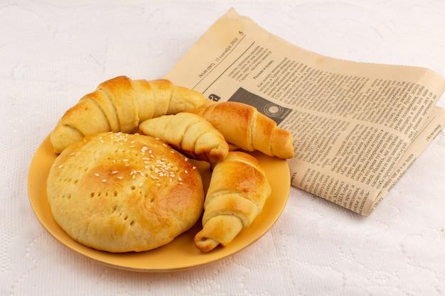 Gebäck und croissants von oben in der orangefarbenen platte zusammen mit tapeten auf dem weißen boden