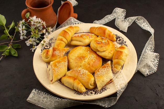 Gebäck und croissants von oben in der weißen platte im dunkeln