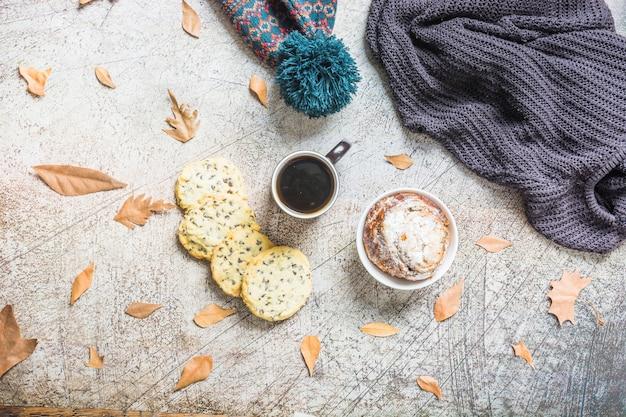 Gebäck und kaffee nahe blättern und warmer kleidung