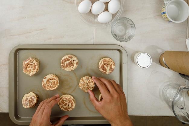 Gebäck zu hause backen hände kekse auf ein blech legen, um sie auf dem herd zu backen