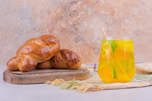 Gebäckbrötchen auf einem holzbrett mit einem glas limonade