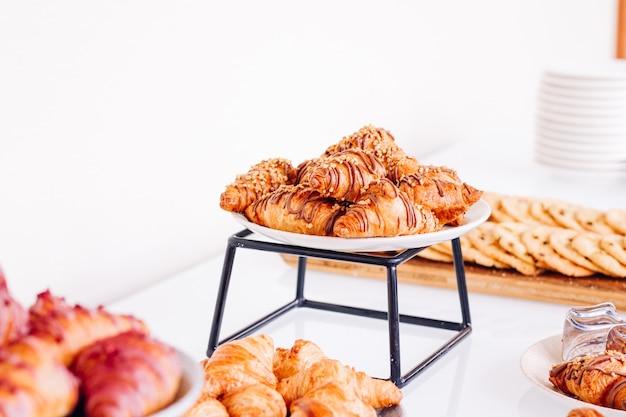 Gebäckkekse und croissants, süße desserts, die bei wohltätigkeitsveranstaltungen serviert werden, getränke und menükonzept als urlaubshintergrundbanner für luxusmarkendesign