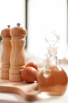 Gebäckzutaten für hausgemachte kuchen und brot in der leeren küche. modernes esszimmer ausgestattet mit kochutensilien mit weizenmehl in glasschüssel und frischen eiern auf dem tisch