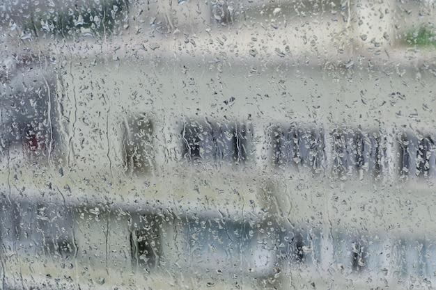 Gebäude auf dem hintergrund eines nassen fensters mit regenstreifen.