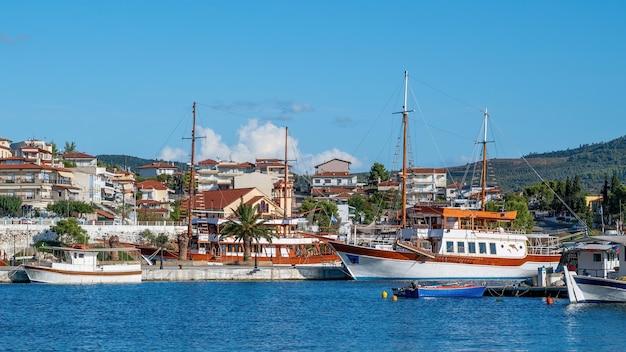 Gebäude auf einem hügel mit viel grün, pier mit festgemachten segelbooten im vordergrund, neos marmaras, griechenland