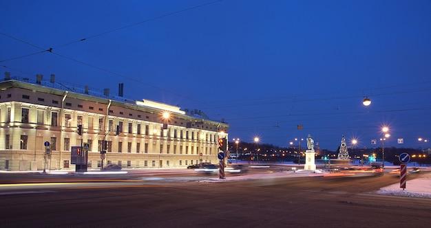 Gebäude mit leuchtenden lichtern im winter und einem weihnachtsbaum auf dem platz.
