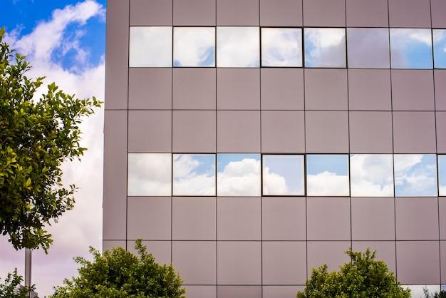 Gebäudefenster mit dem himmel und wolken reflektiert