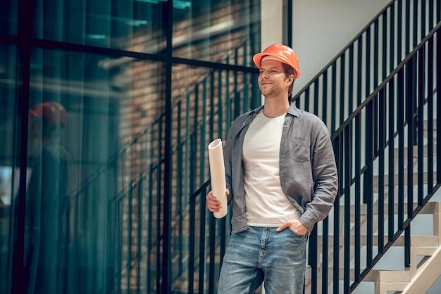 Gebäudefunktion. zufriedener selbstbewusster mann in schutzhelm in jeans, der mit papierrolle in der nähe von treppen steht