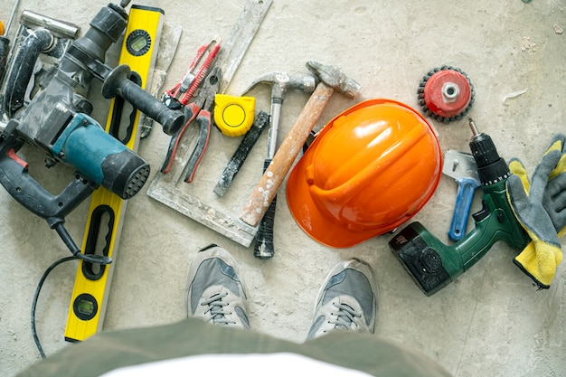 Gebäudehintergrund mit werkzeugen auf dem betonboden.