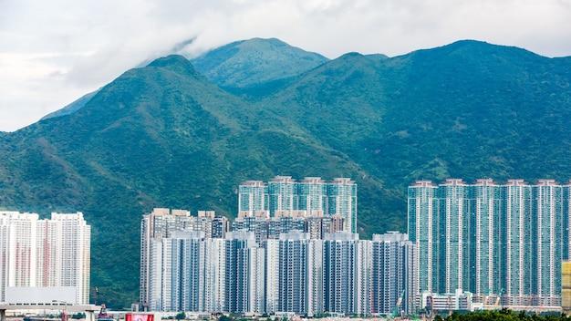 Gebäudekondominium- und gebirgshintergrund in hong- kongporzellan