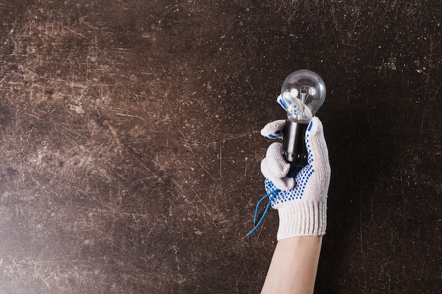 Geben sie arbeitshandschuhe mit einer glühbirne auf einem dunklen marmorhintergrund ab.