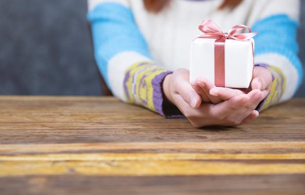 Geben sie ein geschenk auf hölzernem hintergrund, draufsicht