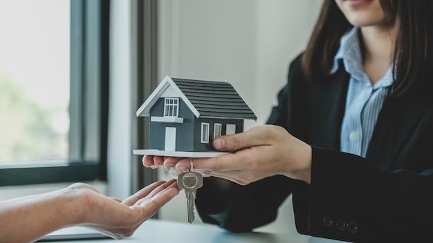 Geben sie einem immobilienmakler das hausmodell und erklären sie der käuferfrau den geschäftsvertrag, die miete, den kauf, die hypothek, das darlehen oder die hausversicherung.