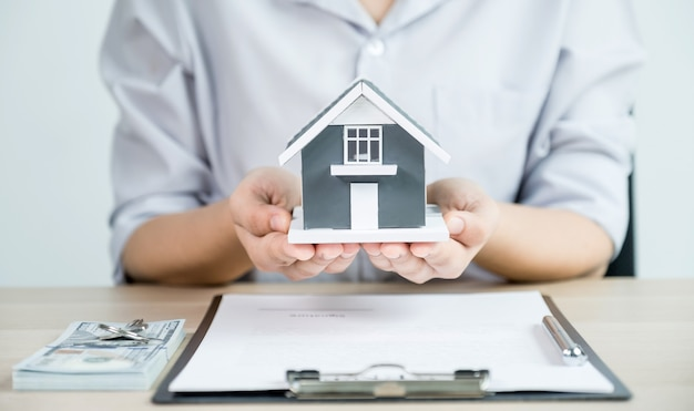 Geben sie einen immobilienmakler, halten sie das hausmodell und erklären sie den geschäftsvertrag, die miete, den kauf, die hypothek, das darlehen oder die hausversicherung.