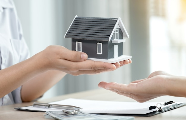 Geben sie einen immobilienmakler, halten sie das hausmodell und erklären sie der käuferfrau den geschäftsvertrag, die miete, den kauf, die hypothek, das darlehen oder die hausversicherung.