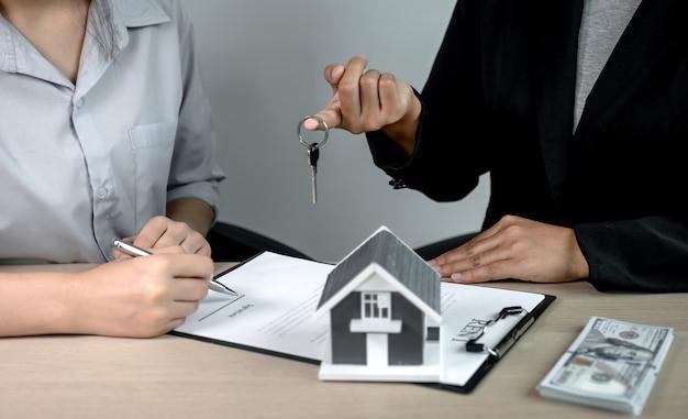 Geben sie einen immobilienmakler, halten sie die schlüssel und erklären sie den geschäftsvertrag, die miete, den kauf, die hypothek, das darlehen oder die hausversicherung.