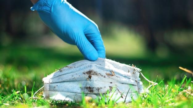 Geben sie einen medizinischen handschuh ab, der eine schmutzige medizinische maske aus dem gras aufhebt