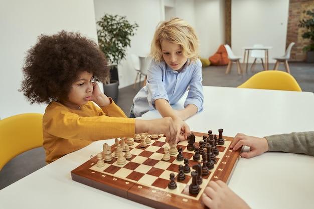 Geben sie kluge kleine jungs ratschläge, die über bewegung diskutieren, während sie am tisch sitzen und schach spielen