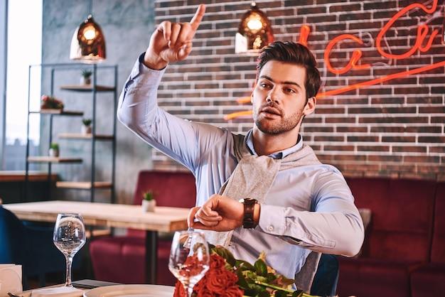 Geben sie mir bitte einen scheck. der mann versucht, eine bestellung aufzugeben, während er im restaurant auf seine freundin wartet. auf dem tisch liegen rote rosen. mann zeigt die zeit auf seiner armbanduhr an