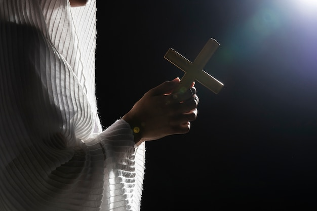 Gebet, das hölzernes kreuz auf vollmond hält