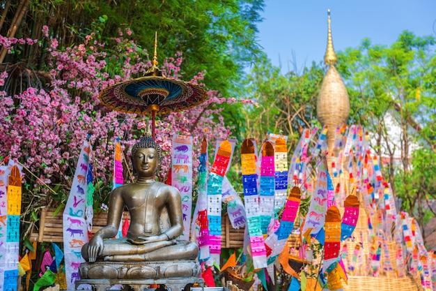 Gebetsfahnen tung hängen mit regenschirm oder traditioneller nordflaggenfall auf sandpagode