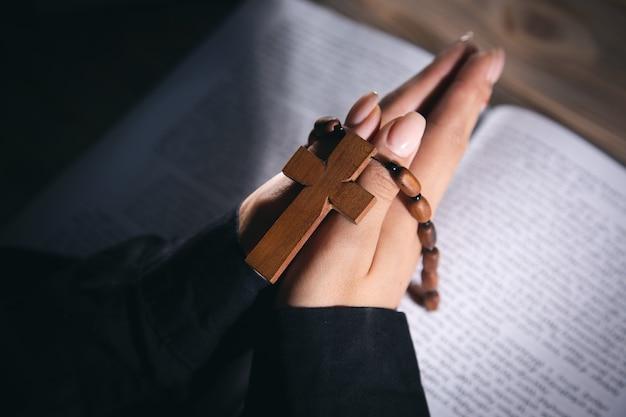 Gebetsfrau mit kreuz auf der bibel