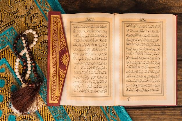 Gebetsperlen und koran auf matte