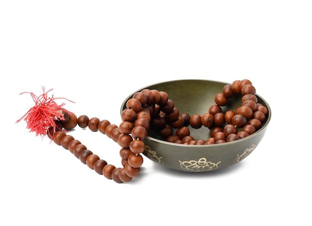 Gebetsperlen und kupfer-klangschale isoliert auf weißer oberfläche. musikinstrument für meditation, entspannung, verschiedene medizinische praktiken im zusammenhang mit biorhythmen, im yoga