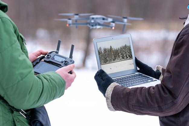 Gebietsplaner überblicken die umgebung mit einer drohne, nahaufnahme einer hand mit einer drohnenfernbedienung und einem laptop, gebietsplanungs- und überwachungskonzept