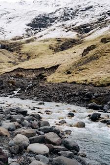 Gebirgsfluss am fuße des berges mit einem schneebedeckten gipfel gelbes trockenes gras auf den bergen