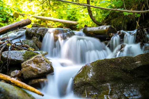 Gebirgsfluss mit kleinem wasserfall mit klarem türkisfarbenem wasser, das zwischen nassen felsblöcken mit dickem weißem schaum herunterfällt.