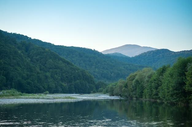 Gebirgsfluss und berge in der untergehenden sonne