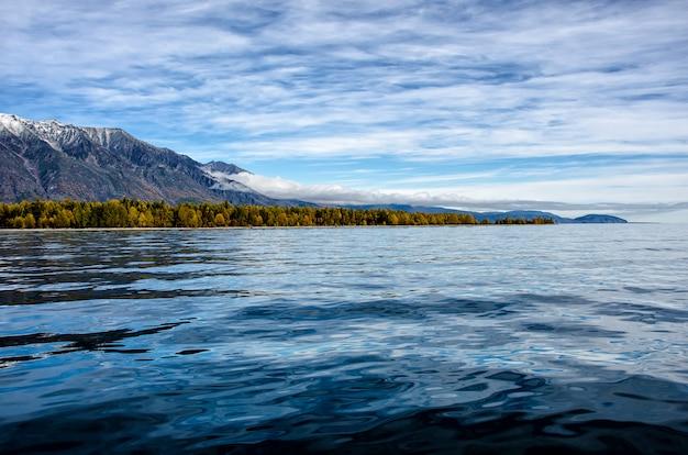Gebirgslandschaft. bewölkter himmel in pastellfarben. romantische seelandschaft. blick auf das meer mit silhouetten von blauen hügeln in einem nebel und herbstwald