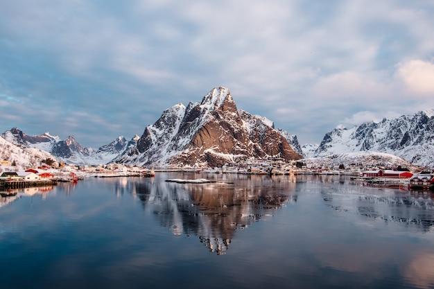 Gebirgsreflexion auf arktischem ozean mit norwegischem fischerdorf bei reine, lofoten-insel, norwegen