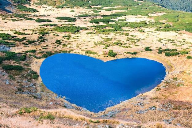 Gebirgssee mit blauem wasser in herzform