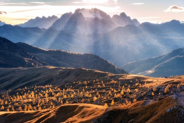 Gebirgstal beleuchtet mit hellen sonnenstrahlen bei sonnenuntergang im herbst in den dolomiten, italien.