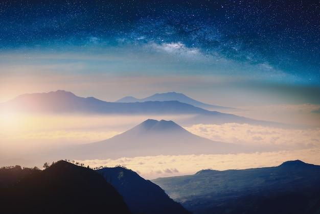 Gebirgszug im nebel mit sonnenlicht und milchstraße.