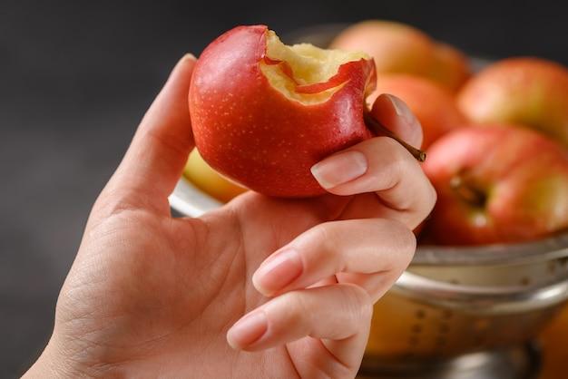 Gebissener apfel in der menschlichen hand auf der metallschale voller roter reifer äpfel.
