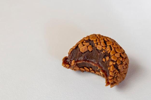 Gebissener brigadeiro, handgemachter schokoladenbonbon lokalisiert auf weißem hintergrund. brasilianisch süß