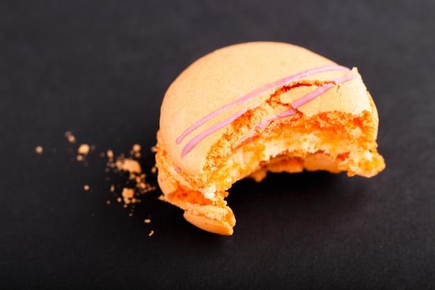 Gebissener orange macaron oder makronenkuchen auf schwarzem hintergrund