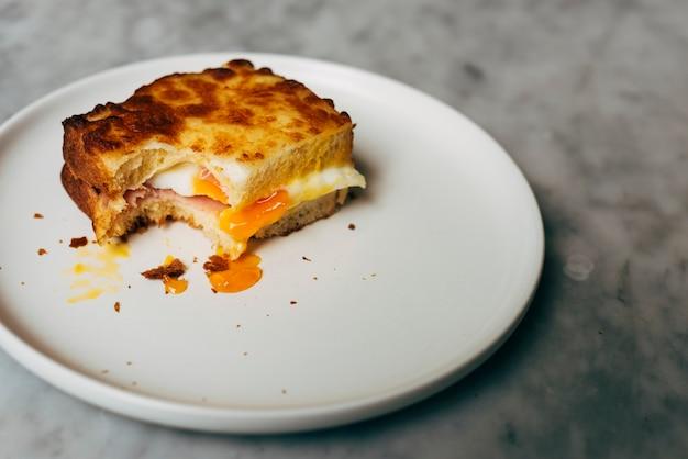 Gebissenes eiersandwich auf einer platte