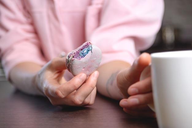 Gebissenes macaron in der hand der frau neben einer tasse tee nahaufnahme textur