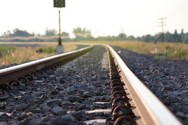 Gebogene eisenbahnlinie mit sonnenuntergang, konzept, zum des ziels zukünftig zu bearbeiten